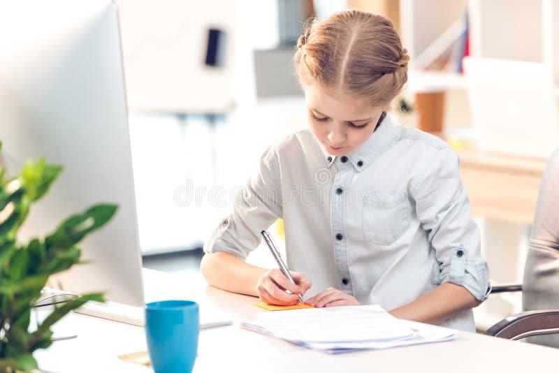 Muchacha que finge ser empresaria y que escribe en nota del palillo en oficina fotografía de archivo libre de regalías
