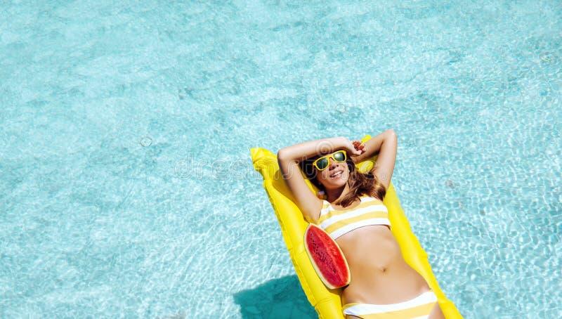 Muchacha que flota en el colchón de la playa y que come la sandía en la piscina del hotel fotografía de archivo libre de regalías
