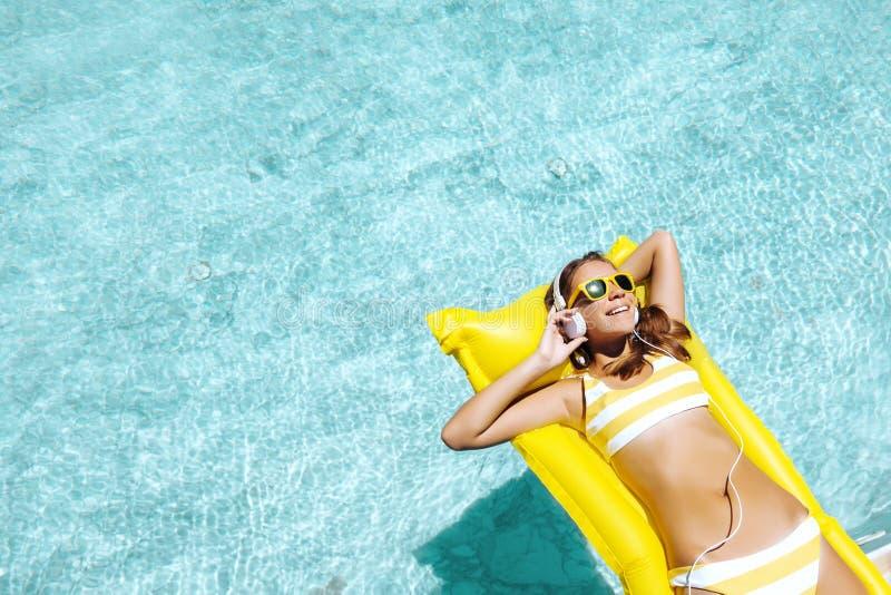 Muchacha que flota en el colchón de la playa y que escucha la música en auriculares en la piscina foto de archivo