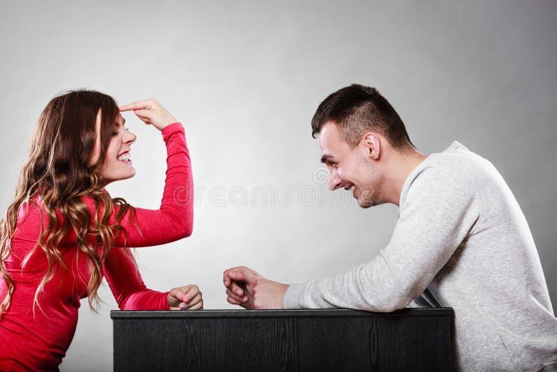 Muchacha que gesticula con el finger que se sienta delante de hombre fotografía de archivo libre de regalías