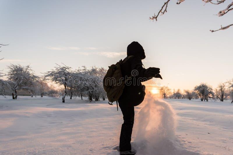 Muchacha que golpea nieve con el pie Paisaje del invierno Puesta del sol imagen de archivo