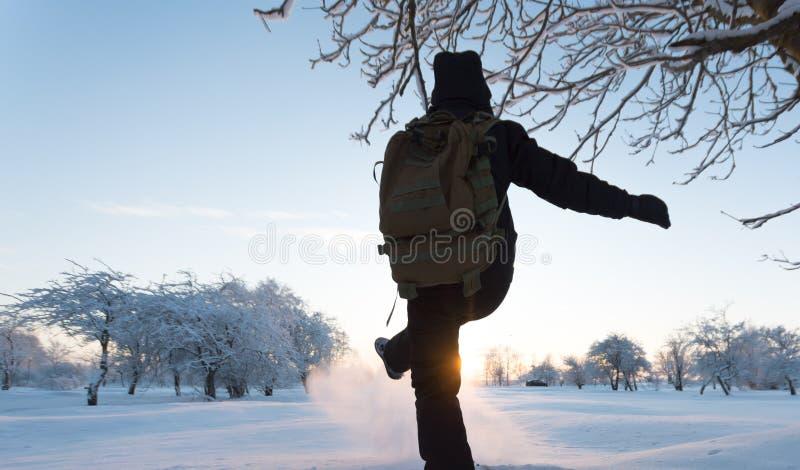 Muchacha que golpea nieve con el pie Paisaje del invierno Puesta del sol imagenes de archivo