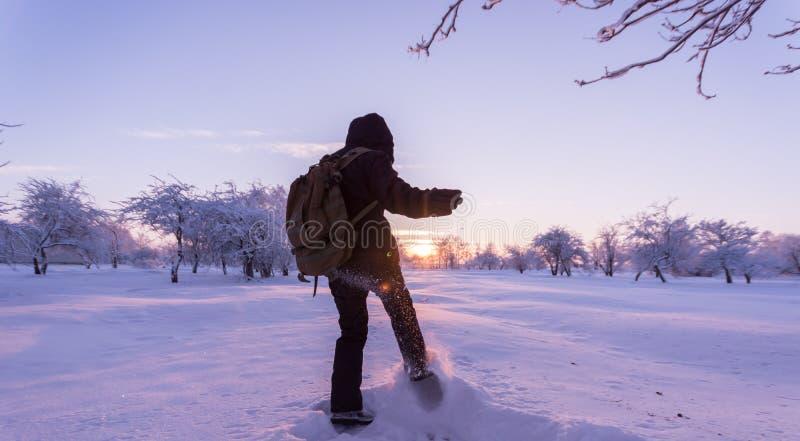 Muchacha que golpea nieve con el pie Paisaje del invierno Puesta del sol fotografía de archivo
