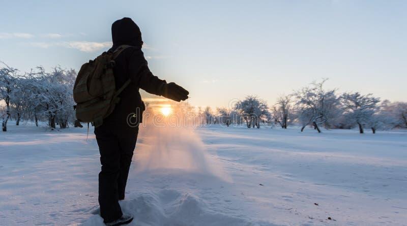 Muchacha que golpea nieve con el pie Paisaje del invierno Puesta del sol fotos de archivo libres de regalías