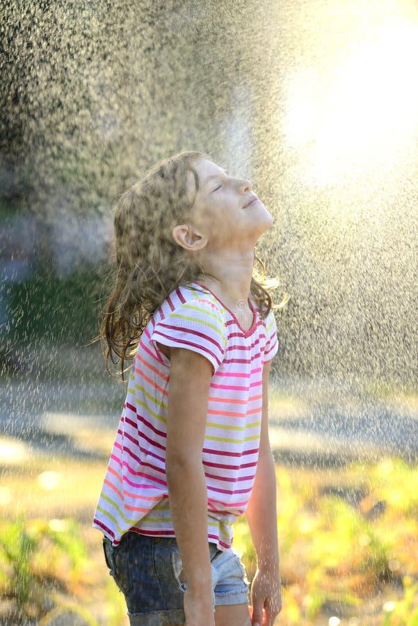 Muchacha que goza de la lluvia ligera del verano imagenes de archivo