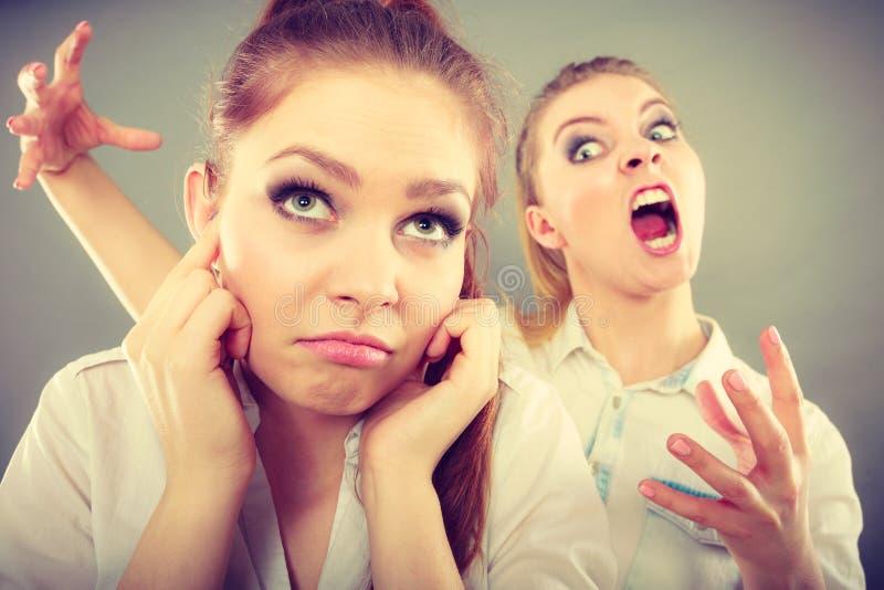 Muchacha que grita en su amigo, closing femenino de la furia sus oídos imágenes de archivo libres de regalías