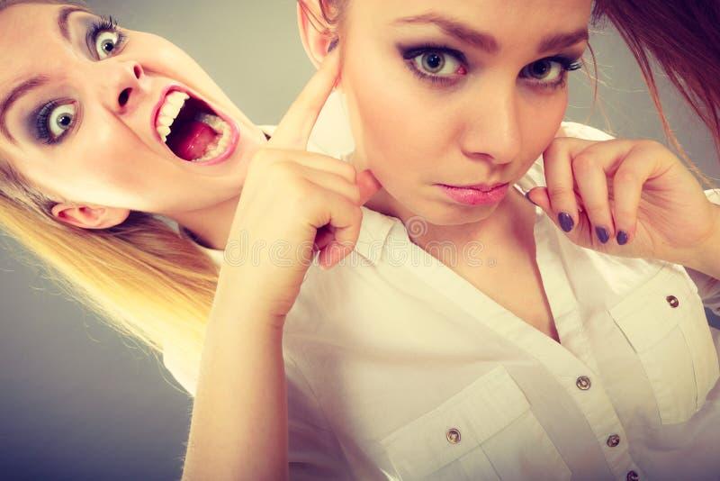 Muchacha que grita en su amigo, closing femenino de la furia sus oídos fotografía de archivo