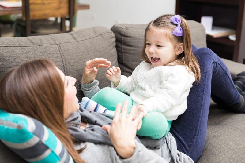 Muchacha que grita mientras que juega Peekaboo con la madre fotos de archivo libres de regalías