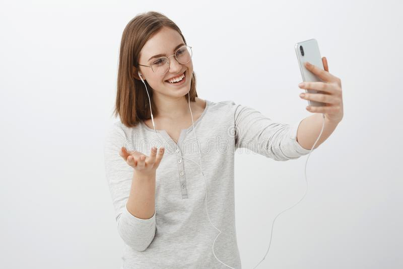 Muchacha que habla con el amigo vía el mensaje video que gesticula con la mano durante la conversación graciosamente que señala l foto de archivo libre de regalías