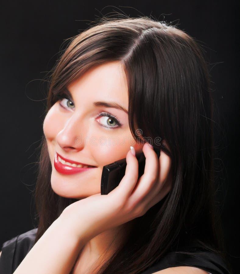 Muchacha que habla en el teléfono sobre negro imagen de archivo libre de regalías