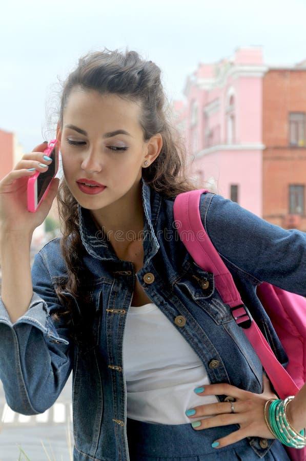 Muchacha que habla en un teléfono celular imagenes de archivo
