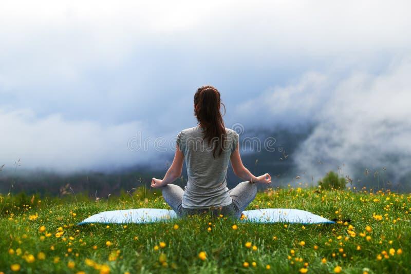 Muchacha que hace actitud del loto del ejercicio de la yoga en césped en montañas fotografía de archivo