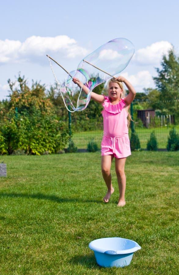 Muchacha que hace burbujas de jabón en jardín imagenes de archivo