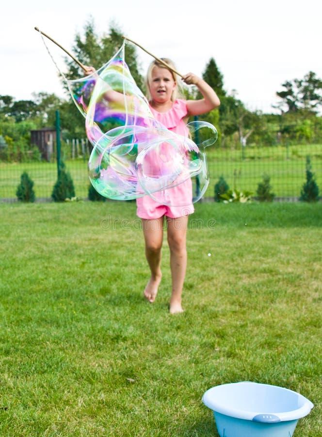 Muchacha que hace burbujas de jabón en jardín foto de archivo libre de regalías