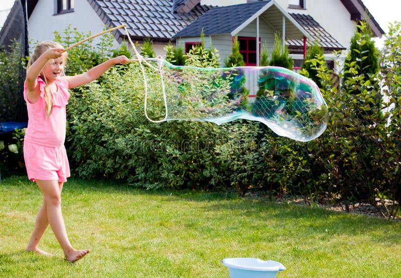 Muchacha que hace burbujas de jabón en jardín fotografía de archivo libre de regalías