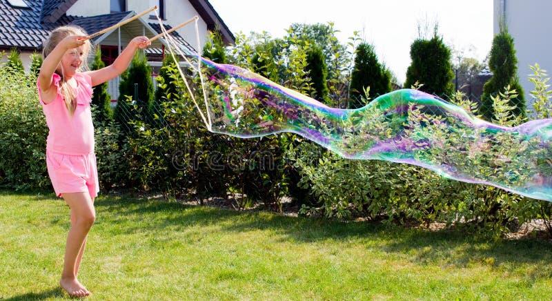 Muchacha que hace burbujas de jabón en jardín imagen de archivo