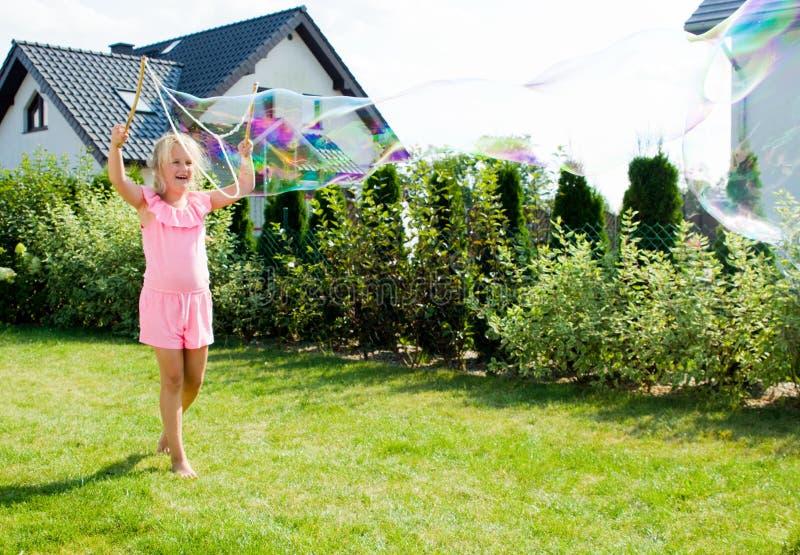 Muchacha que hace burbujas de jabón en jardín fotografía de archivo