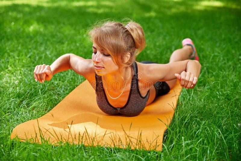 Muchacha que hace ejercicios en la estera en el parque en la hierba verde foto de archivo libre de regalías