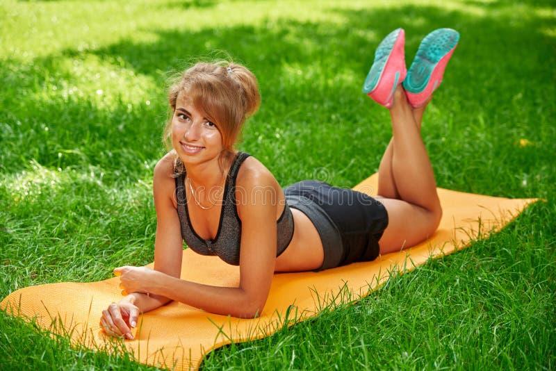 Muchacha que hace ejercicios en la estera en el parque en la hierba verde fotografía de archivo