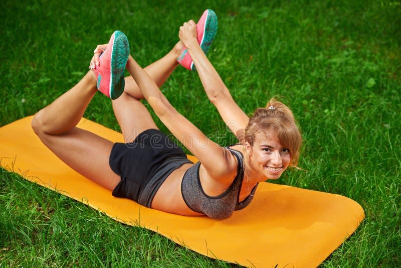 Muchacha que hace ejercicios en la estera en el parque en la hierba verde imagenes de archivo