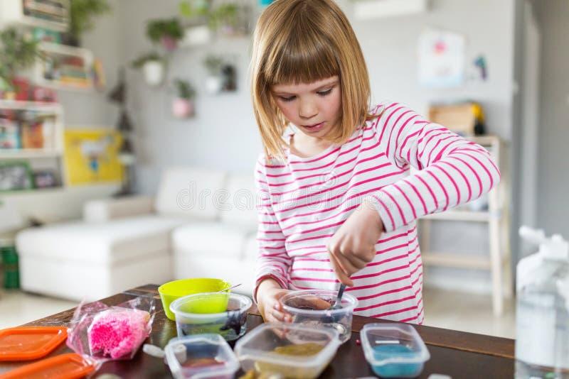 Muchacha que hace el juguete hecho en casa del limo fotografía de archivo libre de regalías