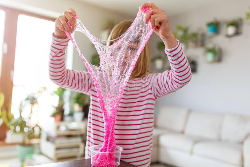 Muchacha que hace el juguete hecho en casa del limo imagen de archivo