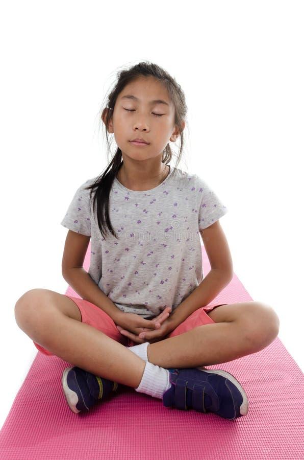 Muchacha que hace el meditaion en la estera rosada de la yoga con el fondo blanco imagen de archivo