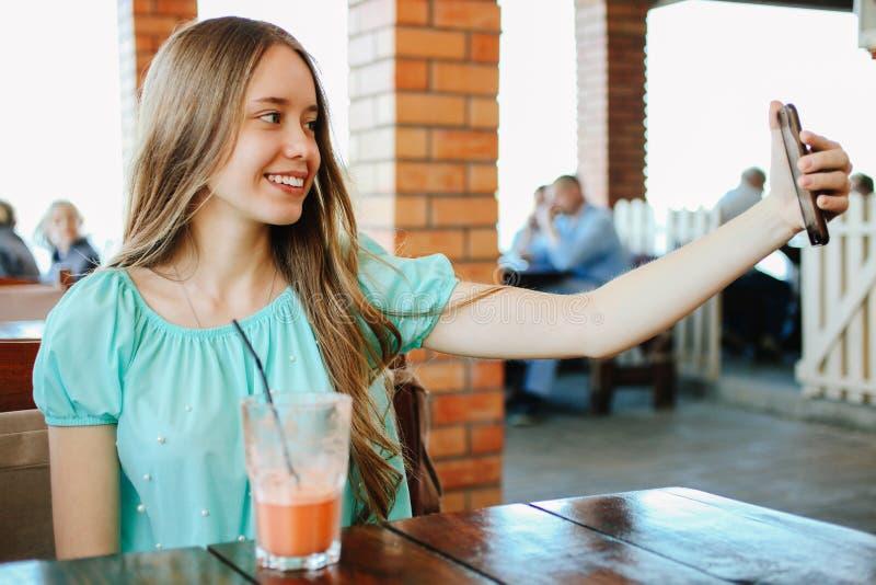 Muchacha que hace el selfie con los smoothies de la fruta imagen de archivo