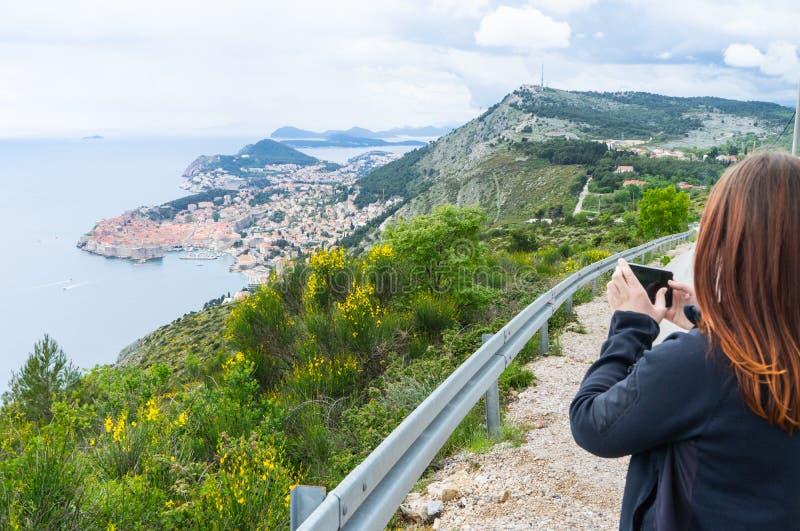 Muchacha que hace imágenes de Dubrovnik en la colina con un teléfono elegante en un pequeño camino a la ciudad vieja en Croacia fotografía de archivo