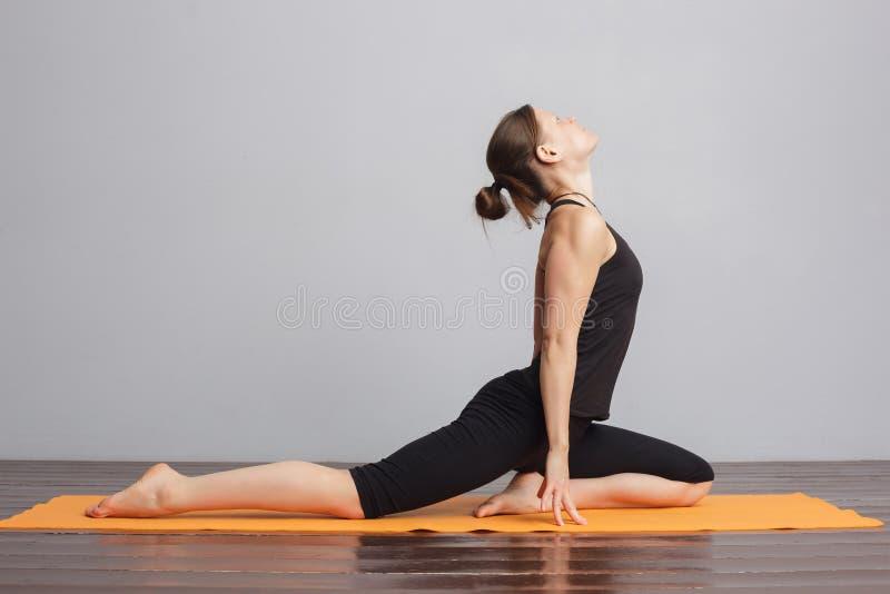 Muchacha que hace la actitud de la paloma, rajakapotasana de la yoga imagenes de archivo