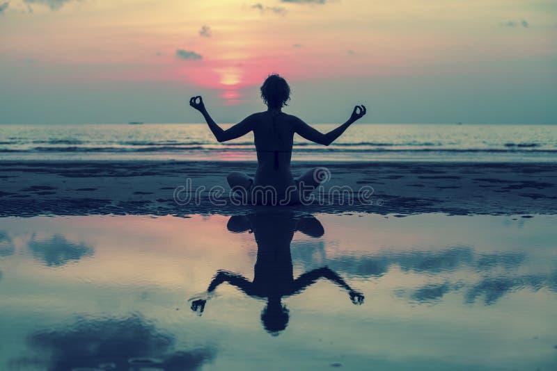Muchacha que hace la meditación en la playa del océano Con la reflexión en agua fotografía de archivo
