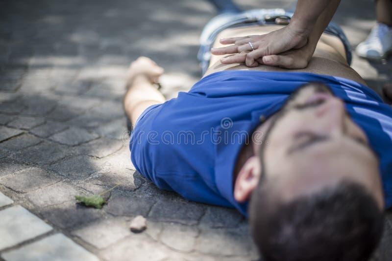 Muchacha que hace la resucitación cardiopulmonar a un individuo inconsciente después de ataque del corazón fotografía de archivo