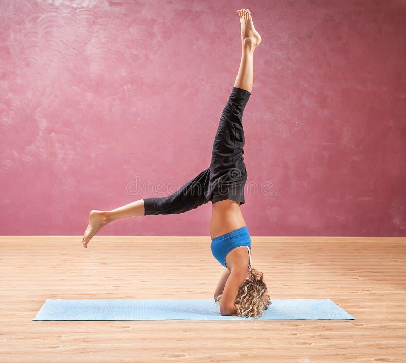 Muchacha que hace la yoga que se coloca en al revés principal fotos de archivo libres de regalías