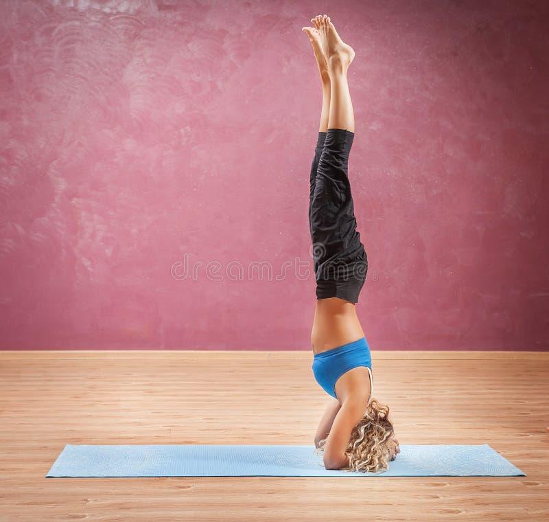 Muchacha que hace la yoga que se coloca en la cabeza imagenes de archivo