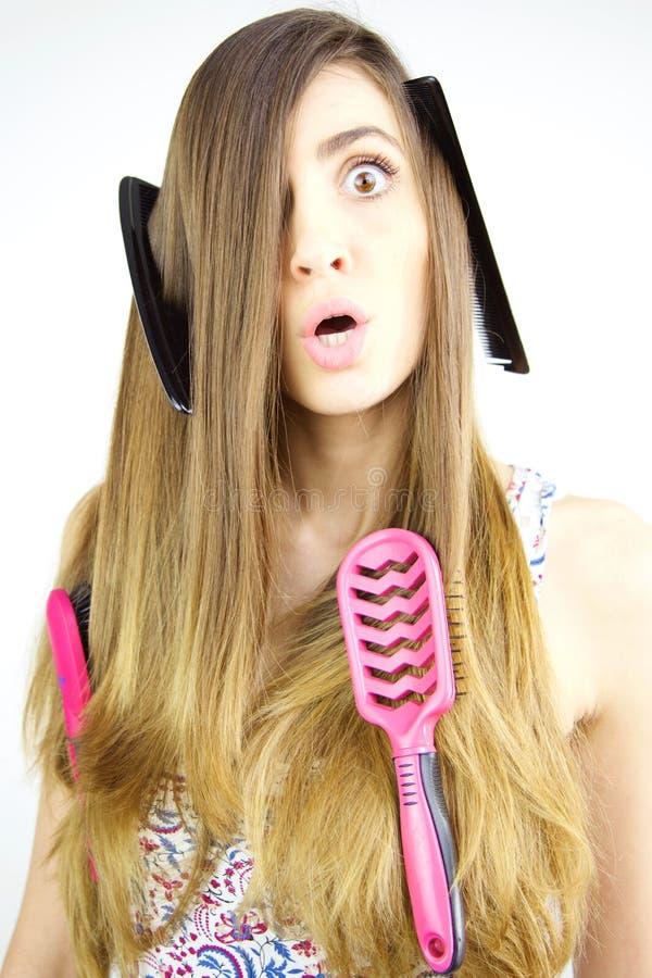 Muchacha que hace las caras divertidas que tienen problema con el pelo largo imagen de archivo libre de regalías