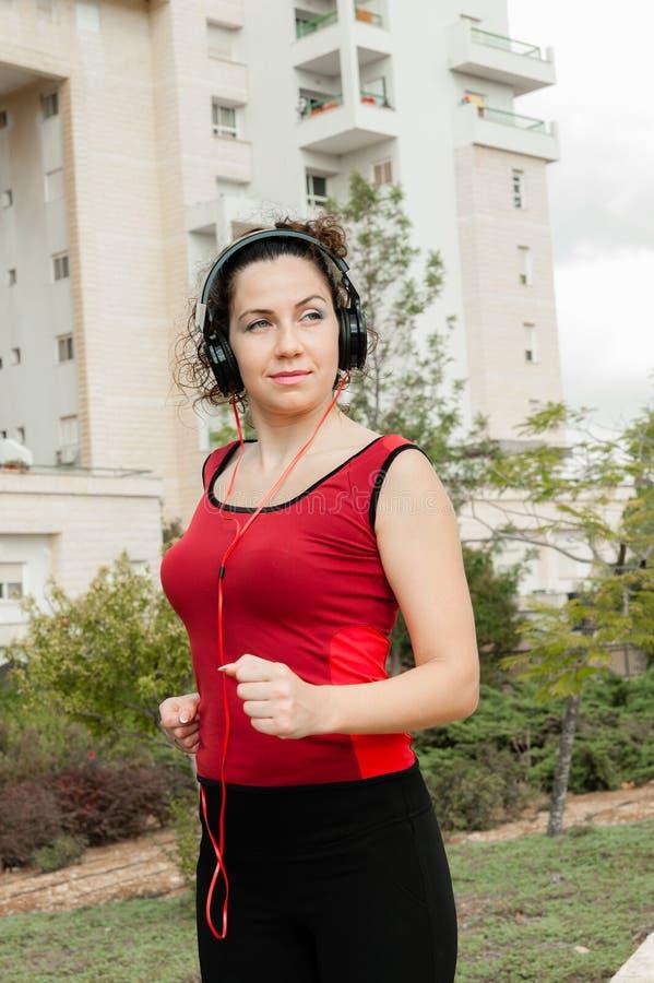 Muchacha que hace los deportes que escuchan la música en los auriculares imagen de archivo libre de regalías