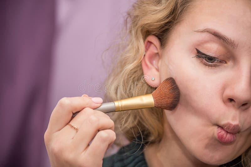 Muchacha que hace maquillaje imagen de archivo