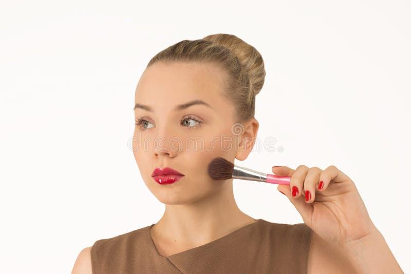 Muchacha que hace maquillaje con el cepillo fotos de archivo