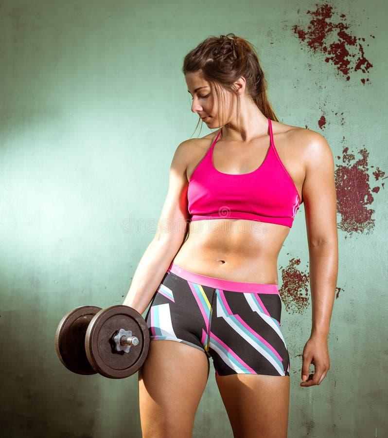 Muchacha que hace rizos del bíceps foto de archivo