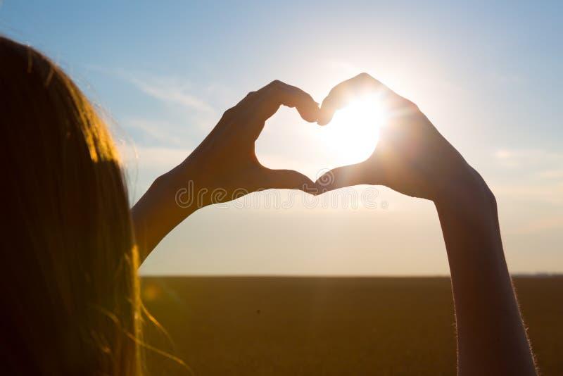 Muchacha que hace símbolo del corazón con sus manos en la puesta del sol en fondo de la naturaleza imagen de archivo