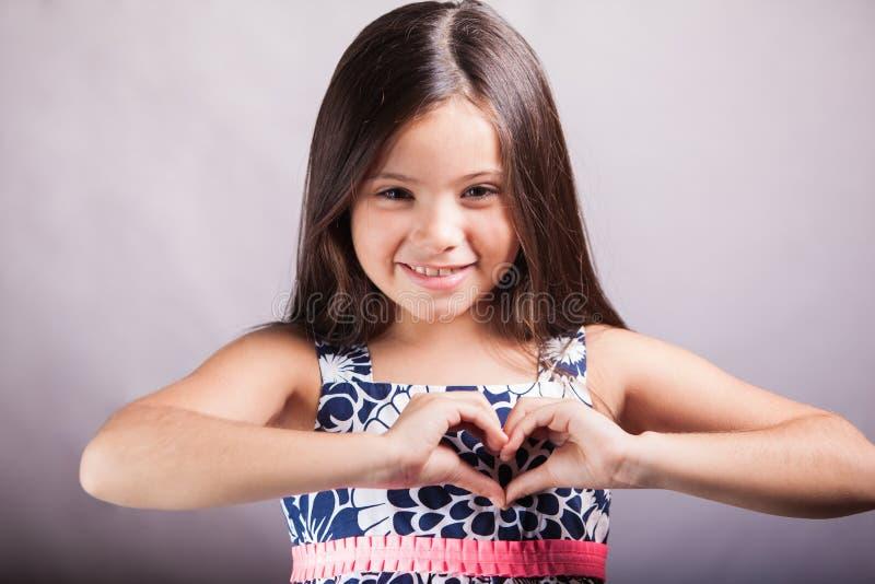 Muchacha que hace un corazón con sus manos fotografía de archivo libre de regalías