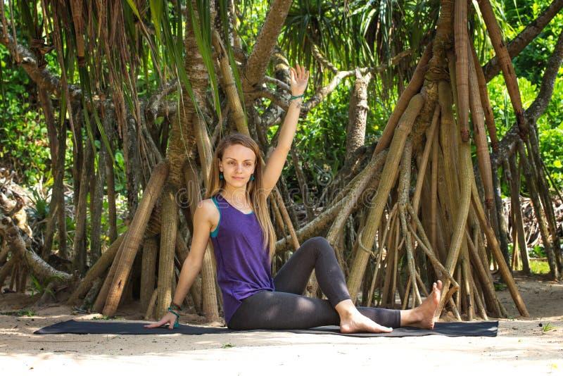Muchacha que hace yoga debajo de las palmeras fotos de archivo