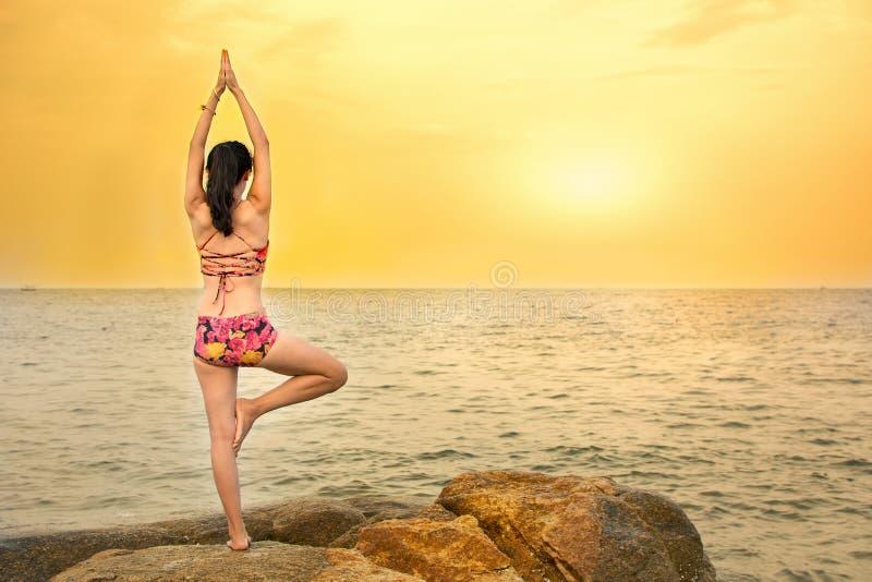 Muchacha que hace yoga en la playa fotografía de archivo