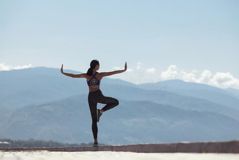 Muchacha que hace yoga por la mañana, en la costa por el mar foto de archivo