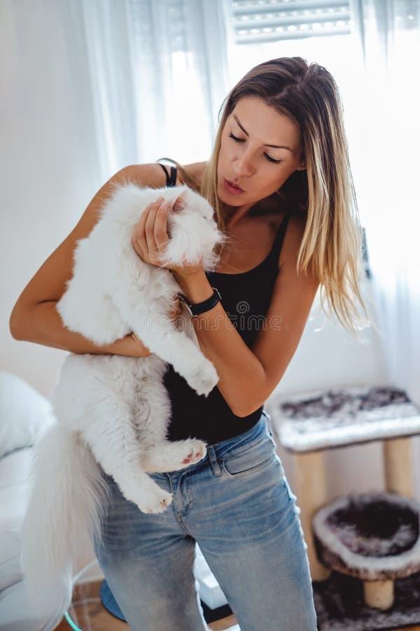 Muchacha que intenta besar un gato en su hogar fotografía de archivo libre de regalías