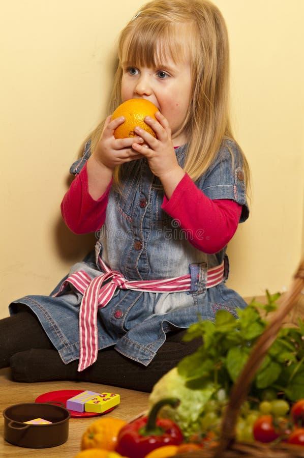 Muchacha que intenta comer una naranja fotos de archivo libres de regalías
