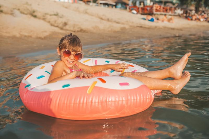 Muchacha que juega con el anillo inflable en agua imagen de archivo
