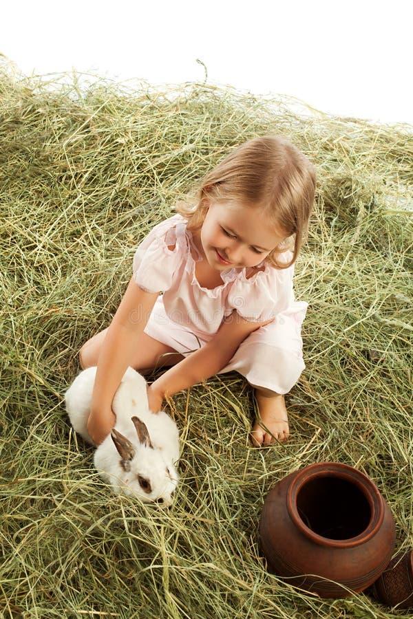 Muchacha que juega con el conejo fotografía de archivo