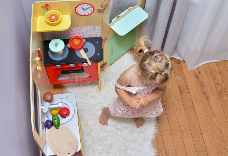 Muchacha que juega con el juguete en una cocina fotos de archivo libres de regalías