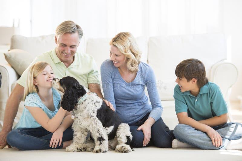 Muchacha que juega con el perro mientras que familia que la mira fotografía de archivo libre de regalías